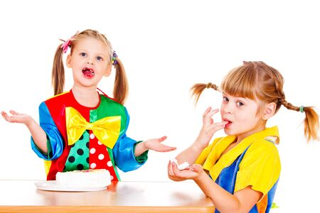Two funny little girls eating cake with their fingers photo