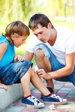 primeros auxilios: Papá ayudar a niño para limpiar sangre de la pierna lesionada