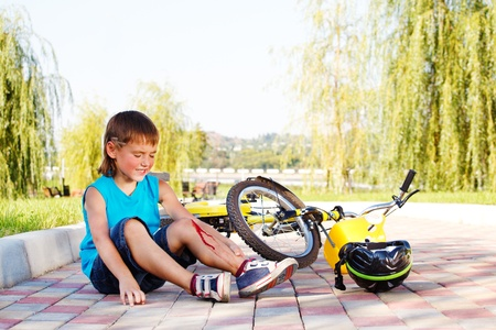 leg injury: Unhappy kid who has fallen off the bike Stock Photo