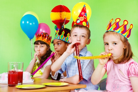 blowout: Cheerful children having fun at birthday party