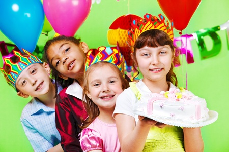 Kids group in party crowns holding birthday cake photo