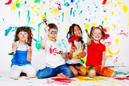 Excited kids with paintbrushes in hands photo