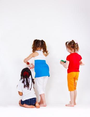 zwart wit tekening: Drie schoolgaande meisjes met behulp van verf te schrijven op de muur
