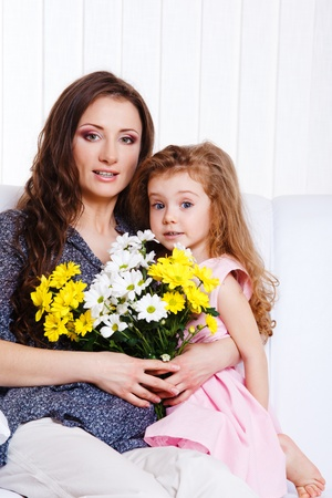 Mother with  birthday flowers in hands, embracing little daughter photo