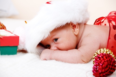 Attractive newborn baby in a huge Santa hat photo