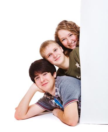 Three teenagers lying behind blank placard