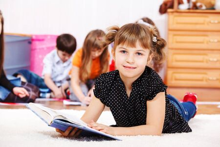elementary age girl: Smiling little girl lies on the floor with a book