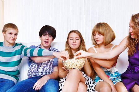 hombre comiendo: Los adolescentes del grupo comiendo palomitas de ma�z juntos