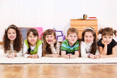 Group of laughing kids lying on floor photo