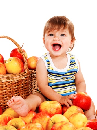 Laughing baby sits among apples photo