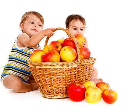small group of people: Two cheerful children playing with apples basket