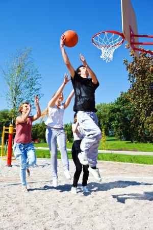 Group of teenagers playing street basketball photo
