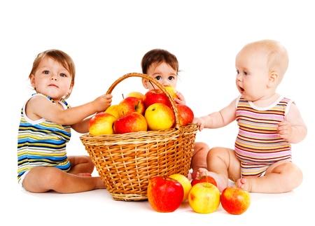 Three babies sit around basket full with apples photo