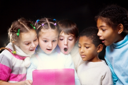 Emotional kids looking inside the shining present box