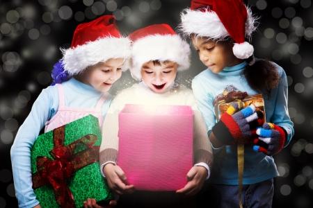 Surprised kids in Santa hats looking inside the present box