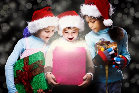 Surprised kids in Santa hats looking inside the present box photo