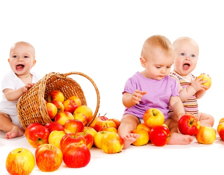 Three sweet cheerful babies playing with apples photo