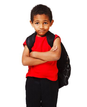 elementary age boy: Sad schoolboy with his arms crossed Stock Photo