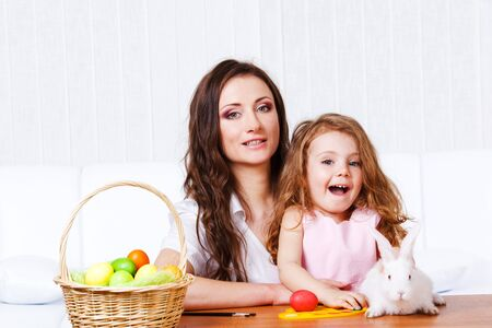 Mother and daughter sit at the table  with Easter eggs and bunny photo