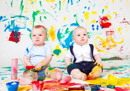 Adorable babies over painted colorful background photo