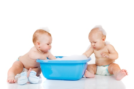 bathing: Blue basin and two babies beside it, washing Stock Photo