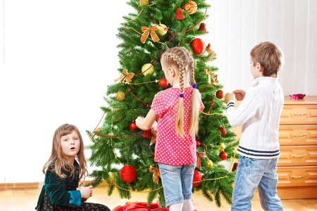 Three kids decorating Christmas tree photo