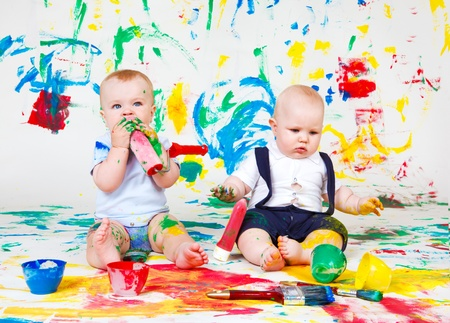 Kids with paint roller and paintbrushes photo
