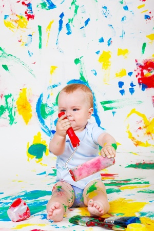 Playful baby painting with a roller photo