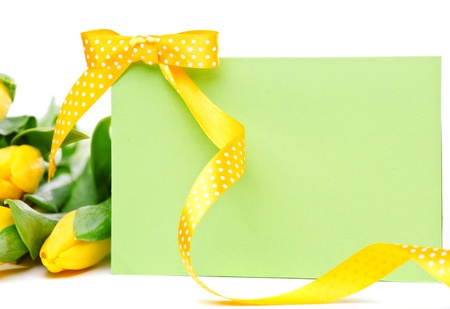 Blank greeting card with yellow ribbon on it and flowers  beside photo