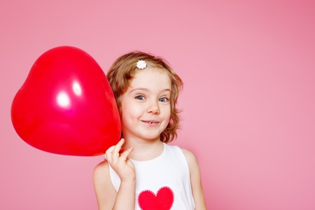 Portrait of a cute smiling preschool girl with a red balloon, over pink