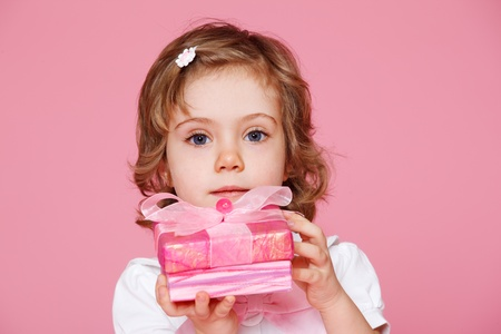 Beautiful preschool  girl holding pink present box Stock Photo - 12193351