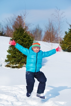 Playful kid jumping into snow photo