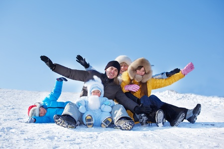 Cheerful parents and their kids sit on snowy hill photo