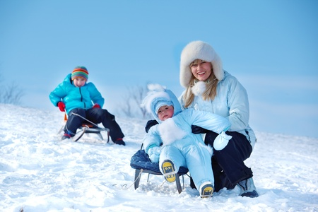 Mother and kids having fun on snowy hill photo
