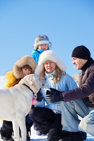 Family playing with dog in a winter park Stock Photo - 12393487
