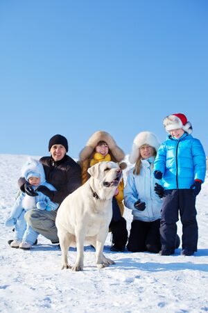 Family on snow and Labrador dog in front photo