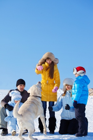 Family playing with Labrador dog in a winter park photo