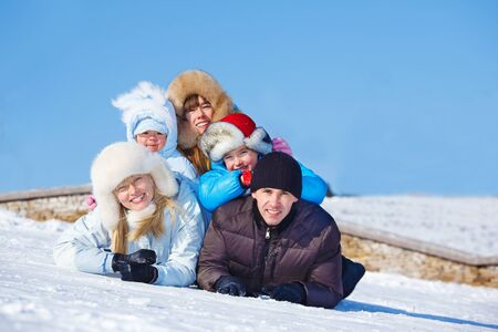 Cheerful parents and three kids lie on snow Stock Photo - 12393486