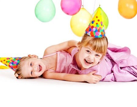 sibling: Girls in birthday hats, laughing