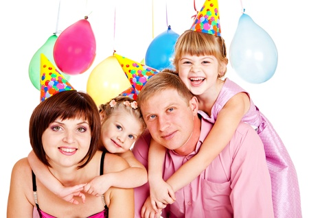 Happy family in party hats celebrating birthday Фото со стока