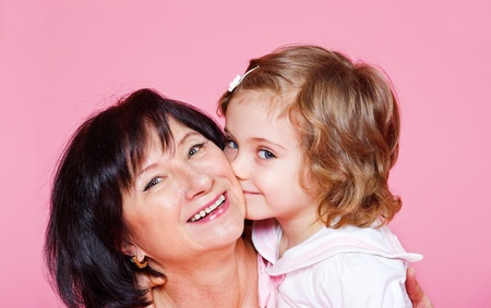 Happy senior woman with her cute granddaughter photo