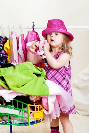 Cute blond girl placing  clothes into shopping cart photo