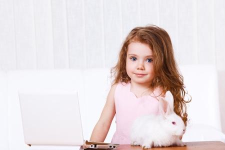 netbook: Kid with rabbit beside white laptop