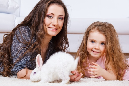 White Easter bunny beside happy mother and daughter Foto de archivo