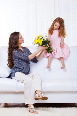 Little girl and woman with flowers sitting on sofa photo