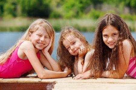 Three girls lie on wooden river bridge photo