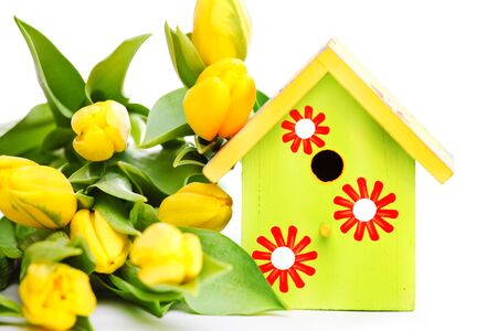 Spring wooden bird house along with  bright yellow flowers photo