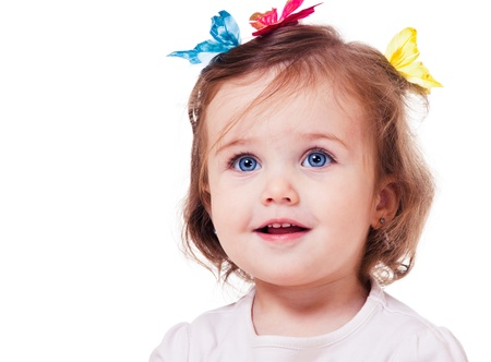 baby girls smiley face: Portrait of a sweet little girl with butterflies on head Stock Photo