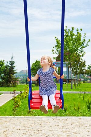 Happy kid on a swing in the playground photo