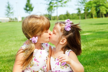 Little sisters kissing each other photo